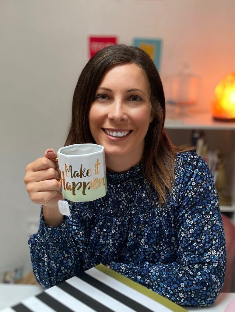 Headshot of Laura holding up a mug